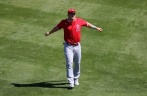 Mike Trout on the grass at spring training spreading his arms like an airplane
